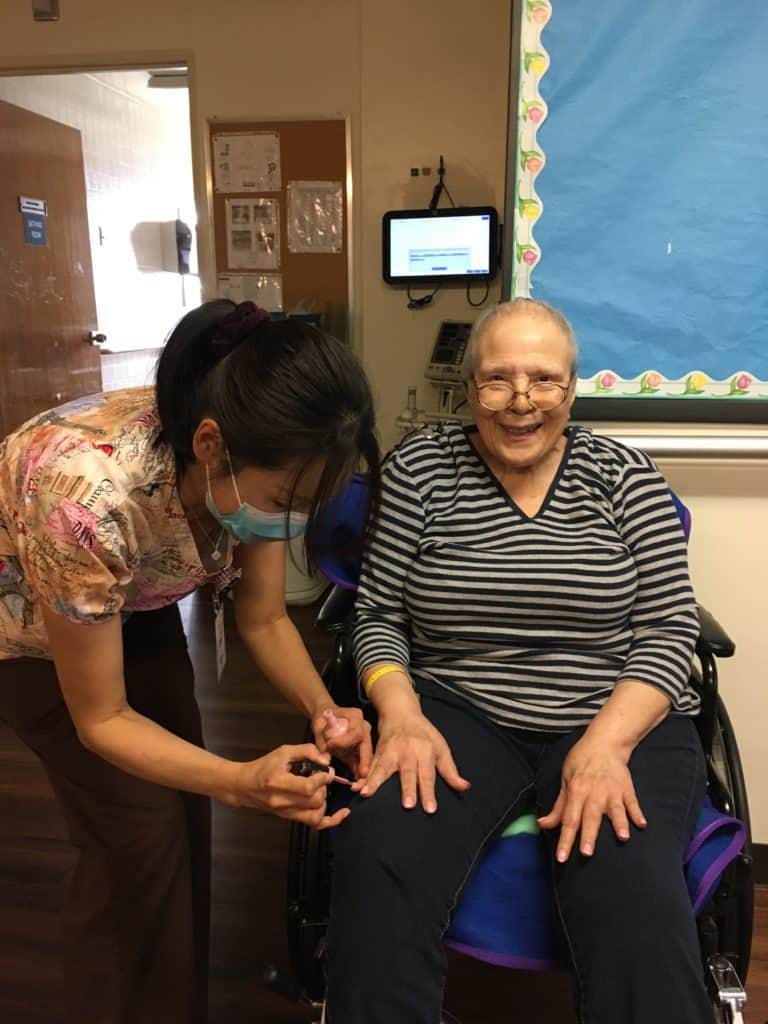 staff with resident doing nails